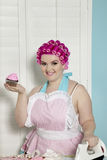 Portrait of happy young woman holding cupcake while ironing Royalty Free Stock Photos