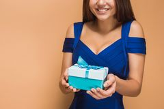 Portrait of happy young woman holding a gifts on brown Stock Photo