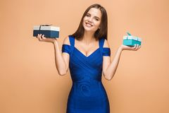 Portrait of happy young woman holding a gifts on brown Royalty Free Stock Photos