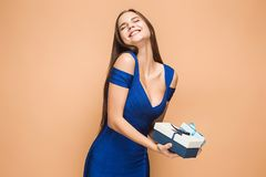 Portrait of happy young woman holding a gifts on brown Royalty Free Stock Photography