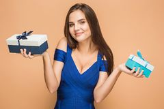 Portrait of happy young woman holding a gifts on brown Stock Images