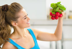 Portrait of happy young woman holding radishes Stock Photography