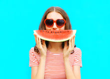 Portrait happy young woman is holding slice of watermelon. Over colorful blue background Royalty Free Stock Photography