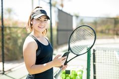 Happy female tennis player during break. Portrait of happy young woman holding tennis racket and mobile phone taking break after training on outdoor court Stock Images