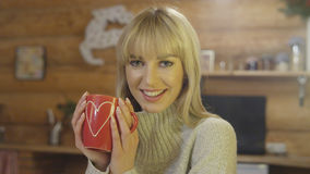 Portrait of happy young woman holding valentines cup at home. Beautiful blonde woman holding cup of tea or coffee and relaxing in winter wooden cabin Royalty Free Stock Image