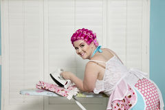 Portrait of happy young woman ironing Royalty Free Stock Images