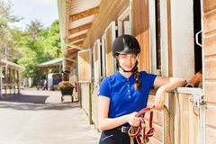 Jockey girl standing by riding stables with reins Stock Photo
