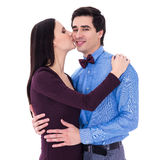 Portrait of happy young woman kissing her husband isolated on wh Stock Image