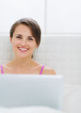 Portrait of happy young woman with laptop in bed Royalty Free Stock Photo