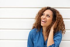 Portrait of a happy young woman laughing outdoors with hand in hair royalty free stock photography