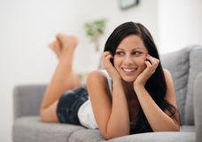 Portrait of happy young woman laying on sofa Royalty Free Stock Photo