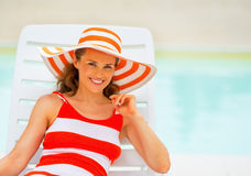 Portrait of happy young woman laying on sunbed Royalty Free Stock Photography