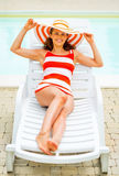 Portrait of happy young woman laying on sunbed Royalty Free Stock Photo