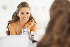 Portrait of happy young woman looking in mirror in bathroom Stock Images