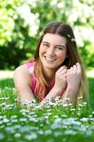 Portrait of a happy young woman lying outdoors on grass and flowers Stock Image
