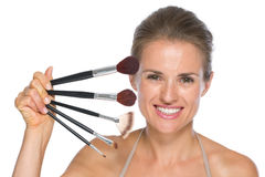 Portrait of happy young woman with makeup brushes Royalty Free Stock Images