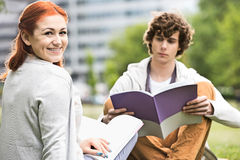 Portrait of happy young woman with male friend studying at college campus. Portrait of happy young women with male friend studying at college campus Stock Photo