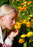 Portrait of happy young woman with marigold. Portrait of beautiful blonde with flowers relaxing outdoors Royalty Free Stock Photo