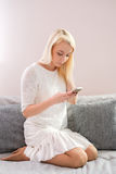Portrait of happy young woman with mobile phone sitting on couch at home.  Royalty Free Stock Image
