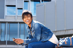 Happy young woman with mobile phone sitting outside and laughing. Portrait of happy young woman with mobile phone sitting outside and laughing Royalty Free Stock Images