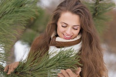 Portrait of happy young woman near fir-tree Stock Photos