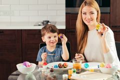 Portrait of happy young woman painting Easter eggs with her adorable little son royalty free stock images