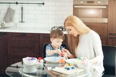 Portrait of happy young woman painting Easter eggs with her adorable little son royalty free stock photos