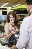 Portrait of a happy young woman paying through credit card in store Royalty Free Stock Photography