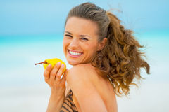 Portrait of happy young woman with pear on beach Royalty Free Stock Photography