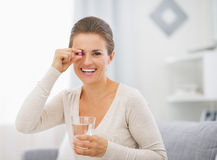 Portrait of happy young woman with pill and glass of water Stock Photo
