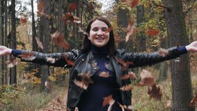 Portrait of a Happy Young Woman Playing With Autumn Leaves In Forest stock video