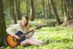 Portrait of a happy young woman playing guitar outdoors Royalty Free Stock Images