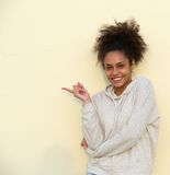 Portrait of a happy young woman pointing finger Stock Photo
