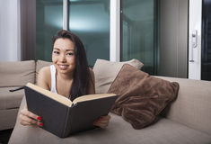 Portrait of happy young woman reading book while lying on sofa Royalty Free Stock Photography