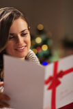 Portrait of happy young woman reading christmas postcard Stock Image