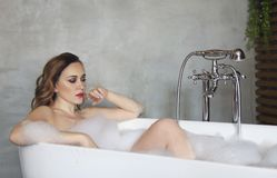 Happy young woman relaxing in bathtub. Portrait of the happy young woman relaxing in bathtub royalty free stock photos
