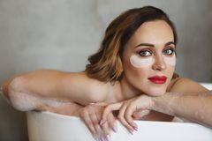Happy young woman relaxing in bathtub. Portrait of the happy young woman relaxing in bathtub stock images