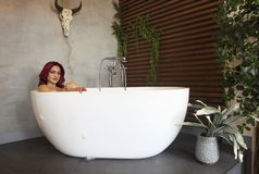 Happy young woman relaxing in bathtub. Portrait of the happy young woman relaxing in bathtub royalty free stock image