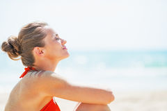 Portrait of happy young woman relaxing on beach Stock Photography