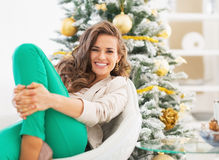 Portrait of happy young woman relaxing near christmas tree Royalty Free Stock Photo
