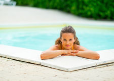 Portrait of happy young woman relaxing in pool Royalty Free Stock Image