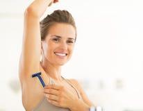 Portrait of happy young woman shaving armpit Stock Photos