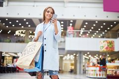 Young Woman Using Smartphone in Sopping Center. Portrait of happy young woman shopping on Black Friday using smartphone and holding paper bags with purchases royalty free stock image