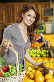 Portrait of a happy young woman shopping in market for fruits Royalty Free Stock Photos