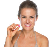 Portrait of happy young woman showing pill Stock Photo