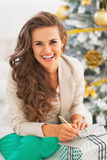 Portrait of happy young woman signing card on christmas present. Box in living room Stock Image