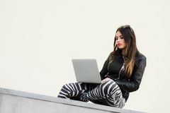 Portrait of a happy young woman sitting on the city stairs and using laptop computer outdoors. Portrait of a pretty woman sitting outdoors Royalty Free Stock Images