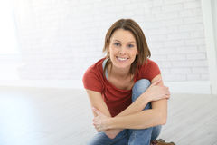 Portrait of a happy young woman sitting on the floor Royalty Free Stock Photos