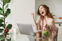 Portrait of a happy young woman sitting with laptop. Computer while having healthy breakfast at the table at home Stock Photos