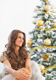 Portrait of happy young woman sitting near christmas tree Royalty Free Stock Photos